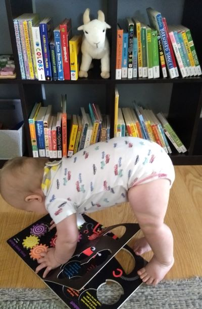 Baby doing downward dog on top of a book.